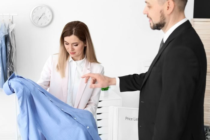 Young businessman giving shirt to dry-cleaner's worker