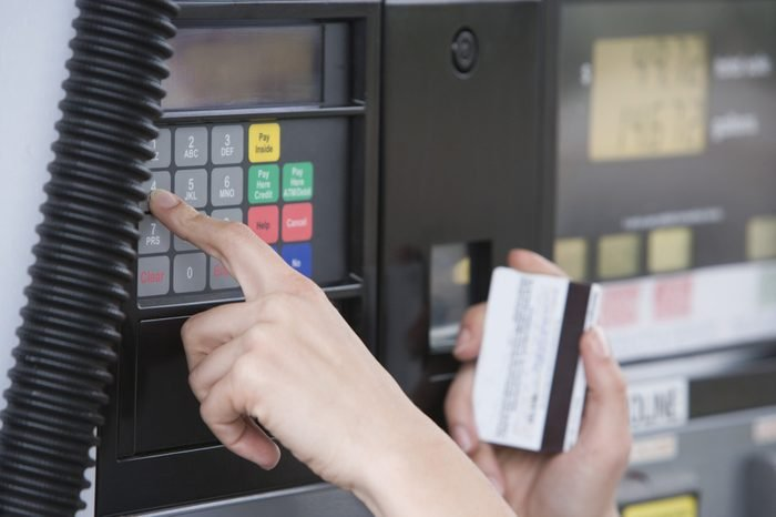 Close-up of woman's hand using ATM machine at fuel station