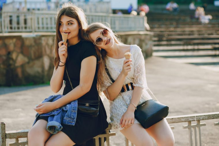two beautiful young girls sitting in the summer park and eating ice cream