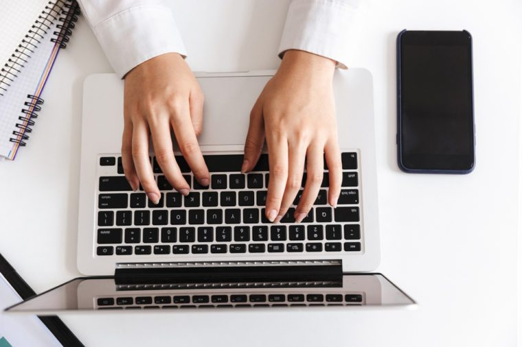 Close up of a woman in white shirt typing on laptop computer on a desk