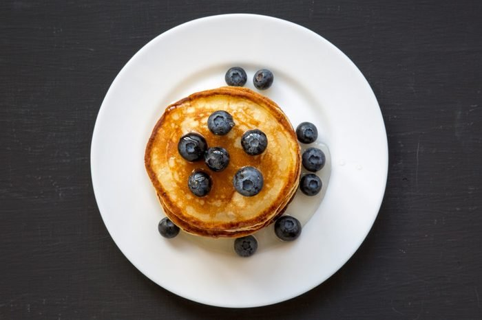 Pancakes with blueberries and honey on white plate on dark wooden background, top view. Flat lay, overhead, from above.