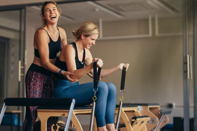 Laughing female trainer helping a woman in pulling stretch bands sitting on pilates training machine. Smiling woman at the gym doing pilates training with her trainer.