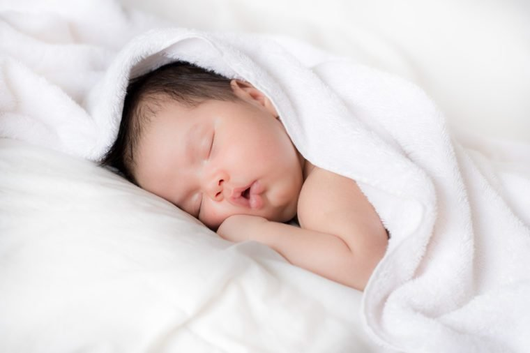 A newly bathed newborn baby sleeps in a white towel