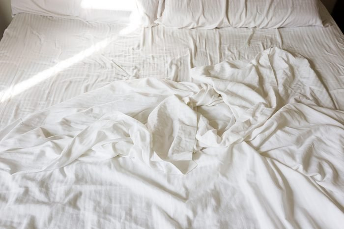 crumpled white sheet in bed