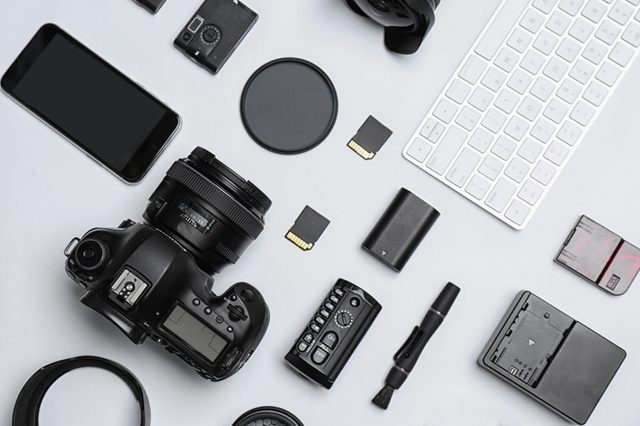 Flat lay composition with equipment for professional photographer on white background