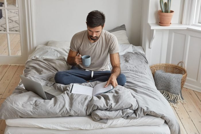 Image of young Caucasian man has morning coffee, sits crossed legs on bed, reads book, prepares for examination, uses laptop computer for surfing internet, dressed in casual domestic clothes.