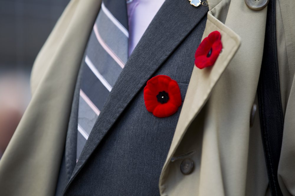 Extreme close-up shot of red flower attached on men's suit.