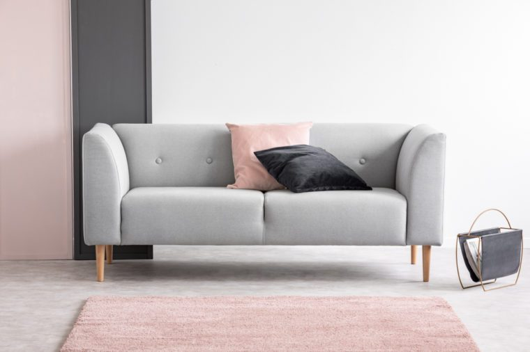 Pastel pink and black design in elegant living room interior with comfortable sofa, real photo with copy space