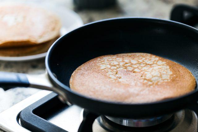 Making american pancakes on frying pan in kitchen interior, preparation breakfast food, nobody