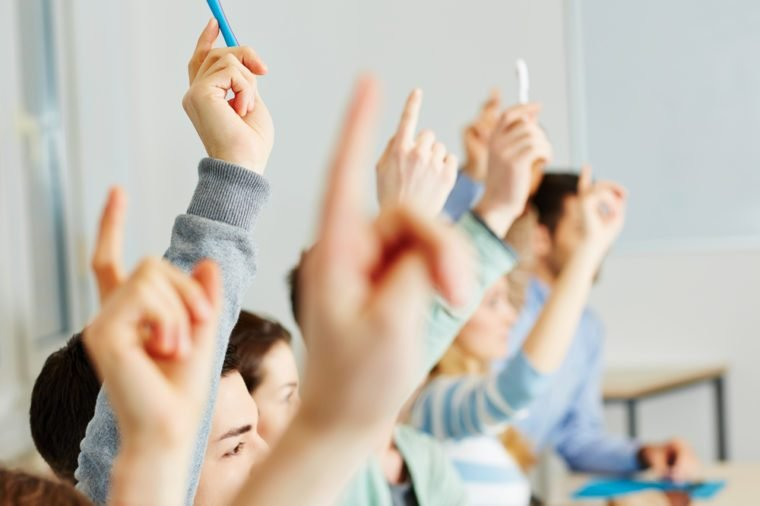 Many students raising their hands in class for an answer