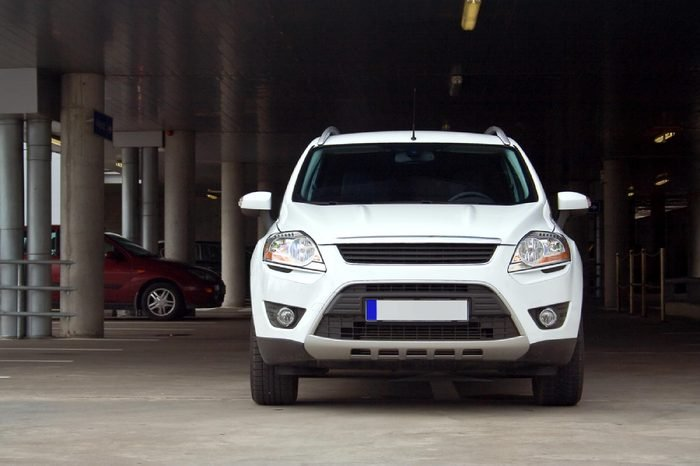 A compact white SUV on a parking lot. Front view.