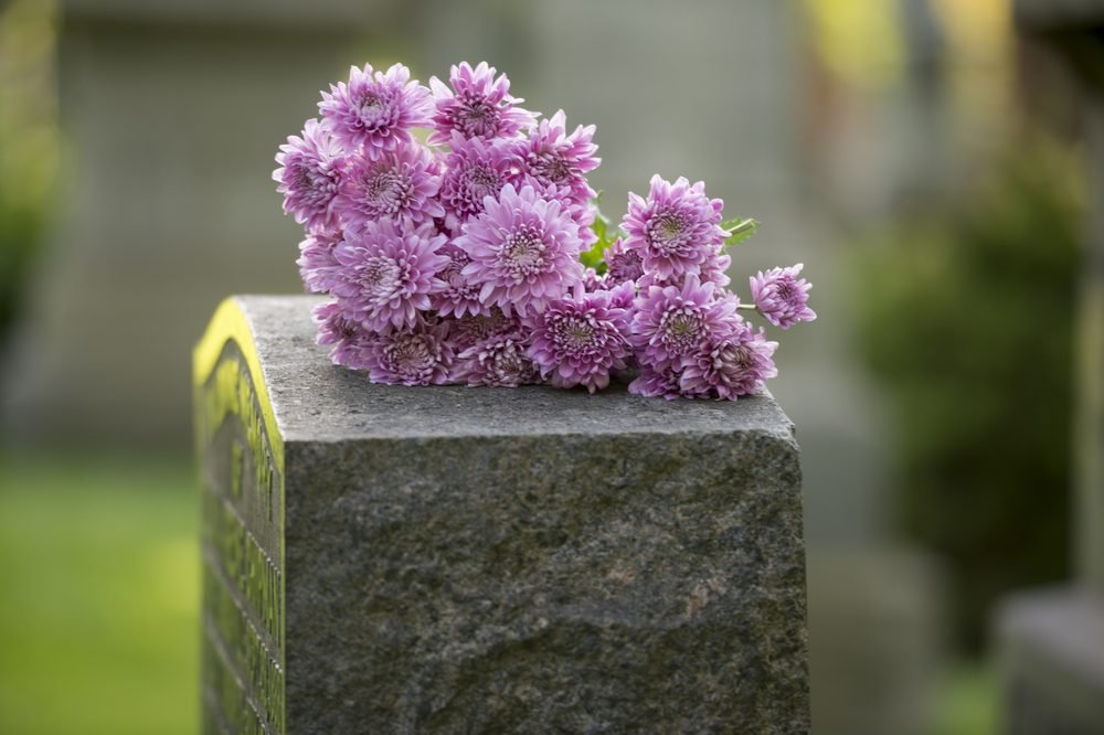 Flowers rest on headstone in cemetery