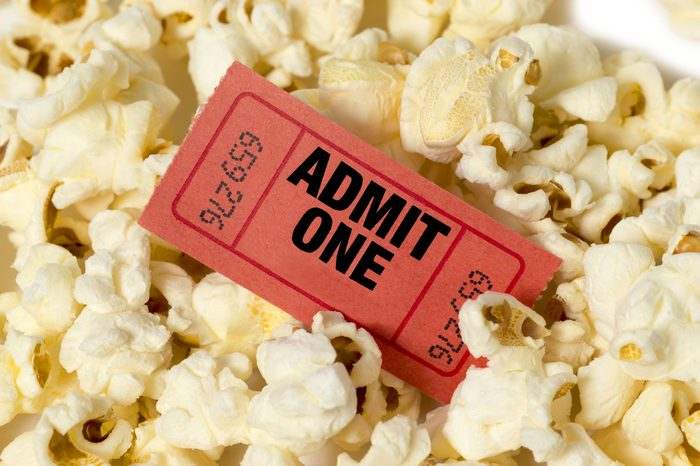Movie Ticket In Center Of Popcorn/ Red Movie Ticket With Popcorn/ Close Up Of Popcorn With Ticket