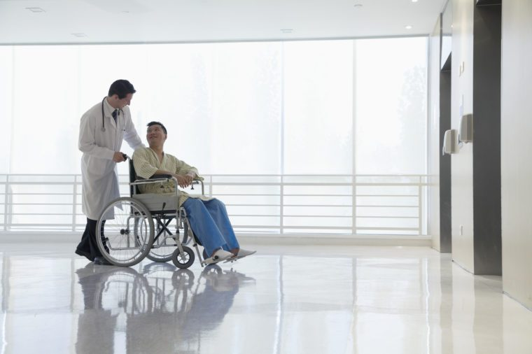 Doctor pushing and assisting patient in the hospital