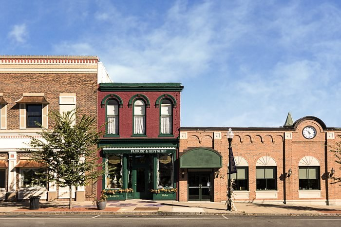 A photo of a typical small town main street in the United States of America. Features old brick buildings with specialty shops and restaurants. Decorated with autumn decor.