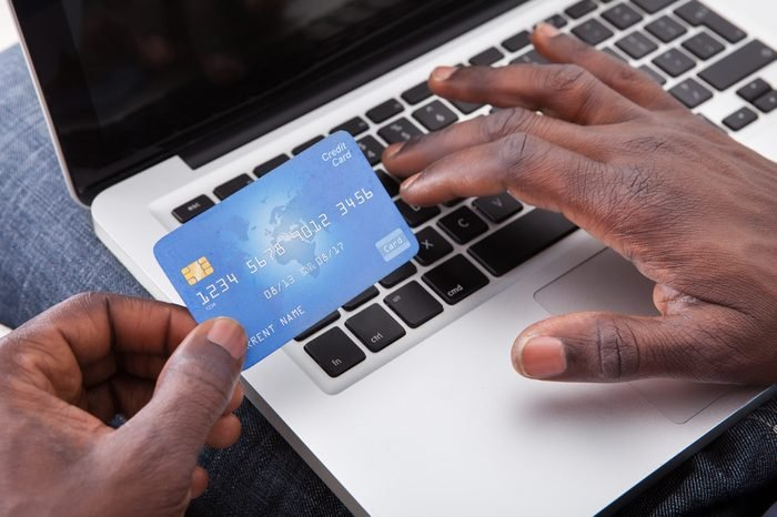 Close-up Of Hand Holding Credit Card And Shopping Online