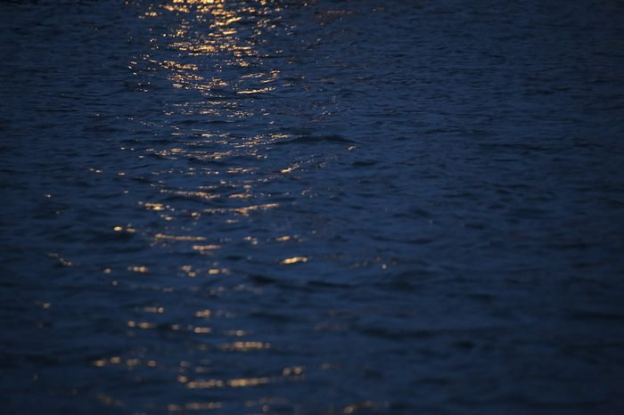 Reflections of yellow light on water in the night.