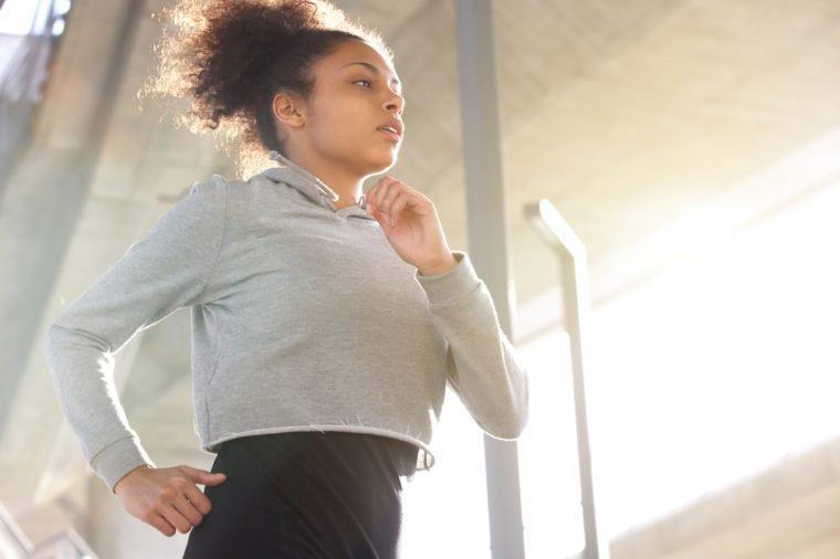 Portrait of an attractive young african american woman running outdoors