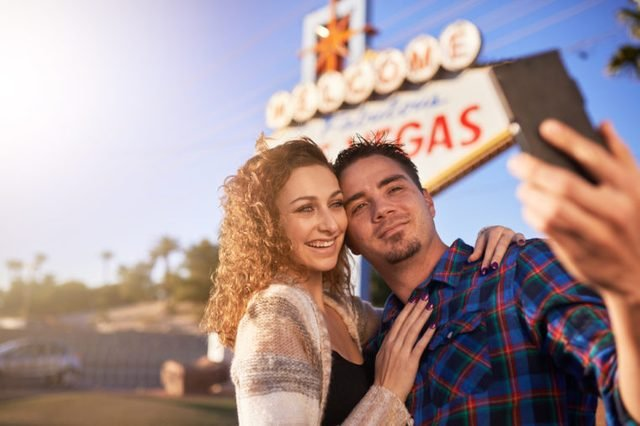 romantic couple taking selfie by welcome to las vegas sign with smart phone
