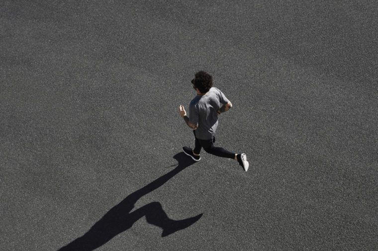 Top view athlete runner training at black road in sportswear at central position. Muscular fit sport model sprinter exercising sprint on city road. Full body length of Caucasian model.