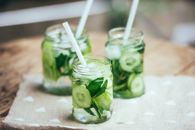 Three retro glass jars of lemonade with cucumber and mint on wooden table