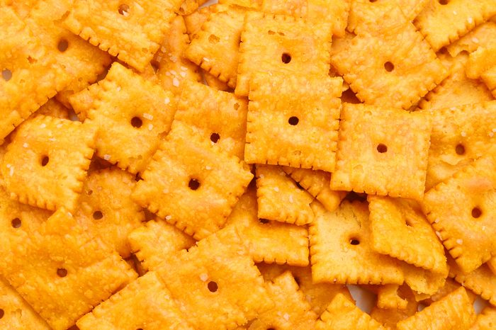 A close view of small square cheese crackers.