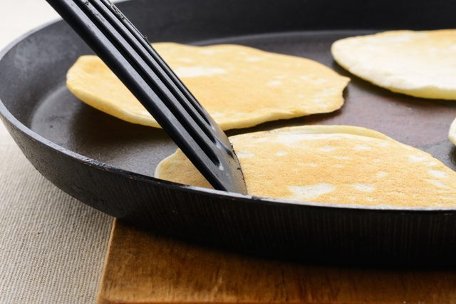 Ruddy pancakes on a black frying pan