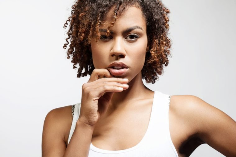 Thoughtful young black woman with clean healthy skin on a white background