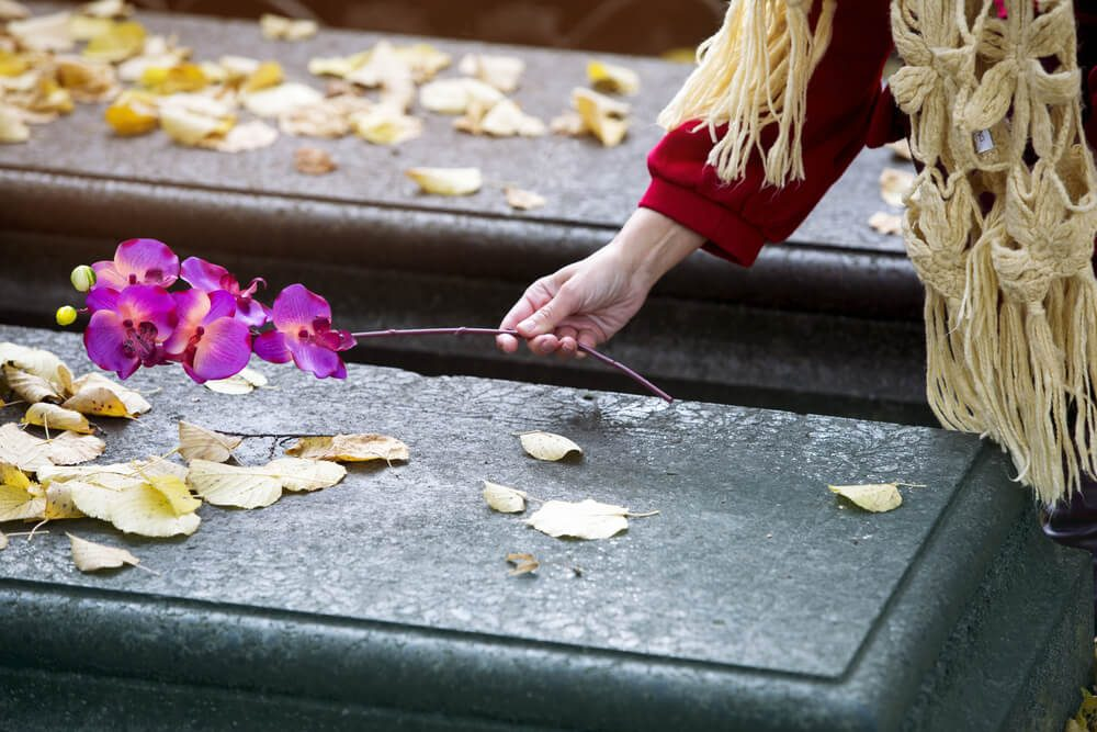 closeup of woman's hand putting a flower on a grave