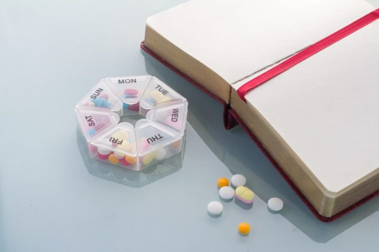 Pills planner with weekly medication capsules in it with notebook on glass top table