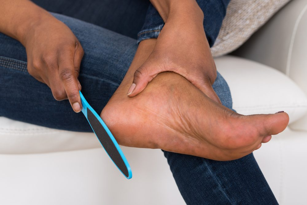 Close-up Of Person's Hand Pedicuring Her Legs
