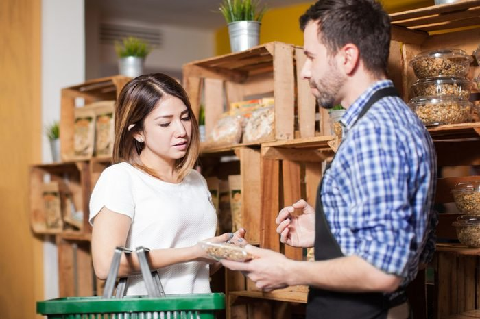 Cute brunette getting some assistance from a store clerk at a local grocery store