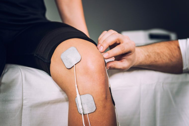 TENS electrodes positioned for knee pain treatment in physical therapy