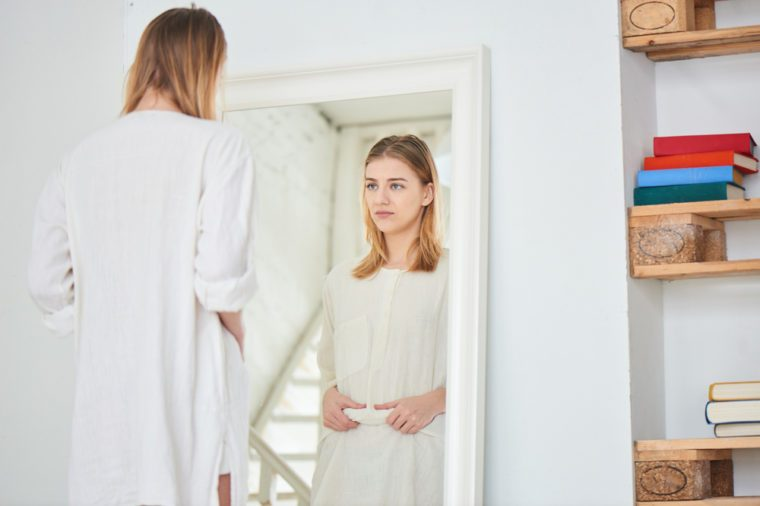 Girl unhappy with their appearance looks in the mirror