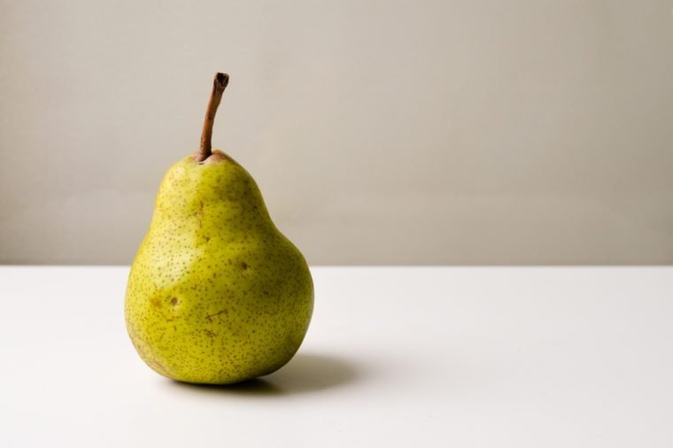 Green and brown pear on a white table against a neutral background