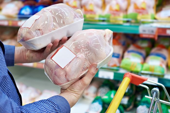 Buyer man chooses chicken meat in a shop