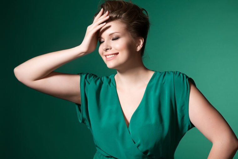 Beautiful laughing plump girl in a green evening dress and hairstyle