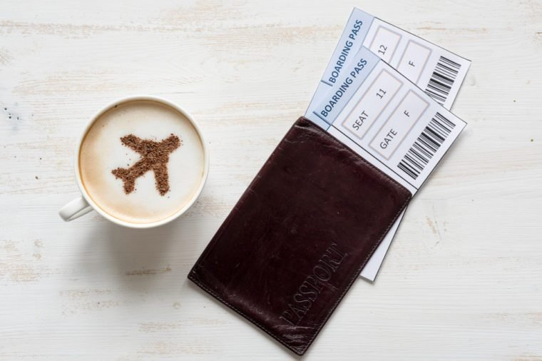 Cup of coffee, passports and no name boarding passes. Airplane made of cinnamon in coffee. Traveling concept. Cappuccino in airport