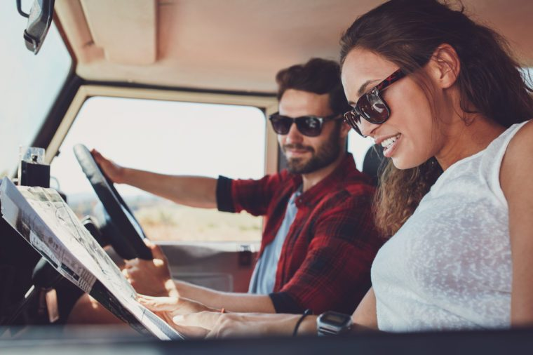 Side view of young couple reading a map for directions. Young man and woman in the car going on roadtrip.
