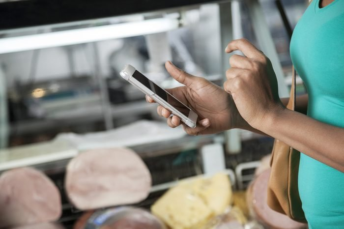 Woman Using Cell Phone In Cheese Shop