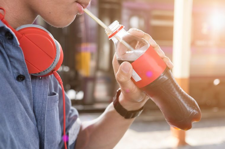 close up man ware headphone and drink soda pop on bottle