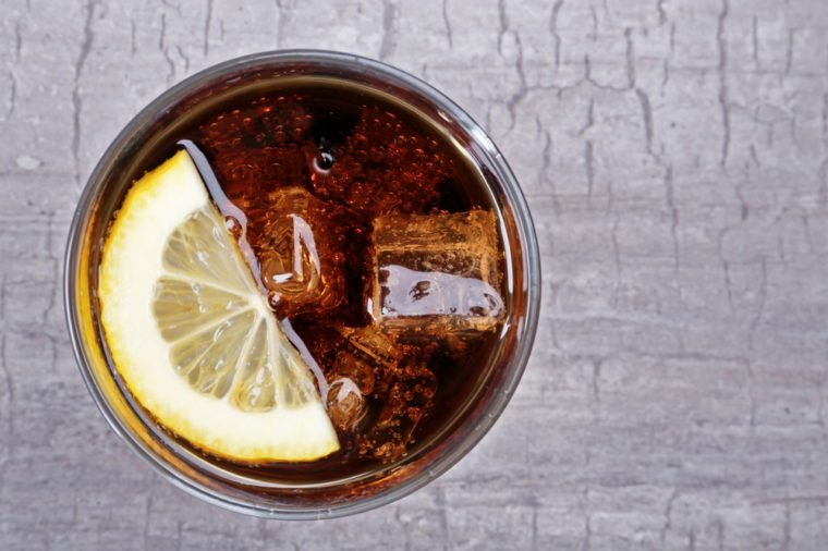 Glass of cola with ice and lemon on rustic wooden background