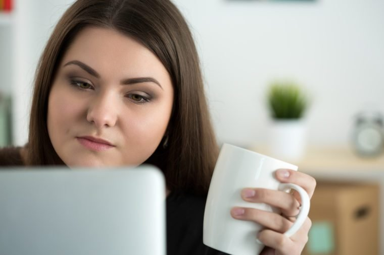 Portrait of young sad or attentive woman looking at laptop monitor and holding white cap of tea.