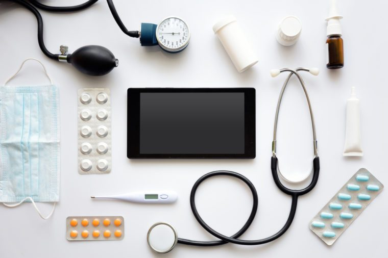 E-medicine concept.Black tablet mock up,together with stethoscope,thermometer,various medications and surgical mask around it,laid flat on top of white surface.
