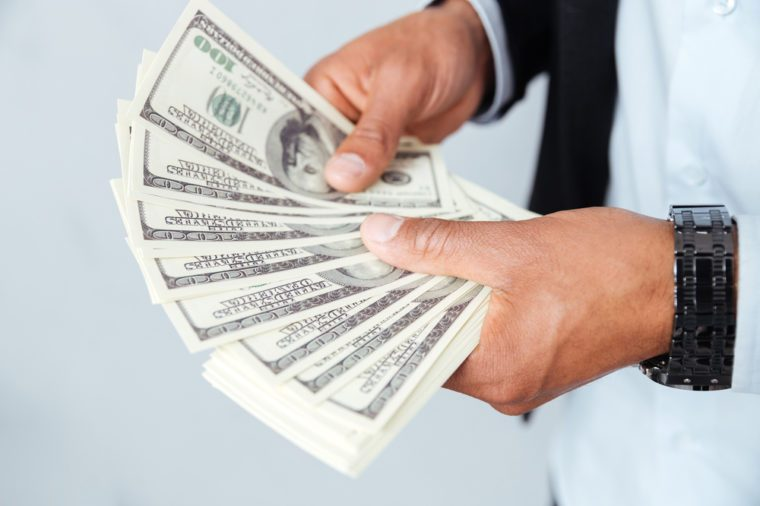 Closeup of hands of african young man holding money