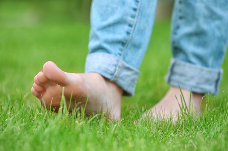 Woman walking barefoot on green grass background