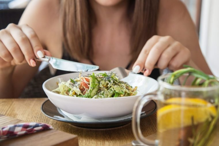 Closeup portrait of female hands eating salad