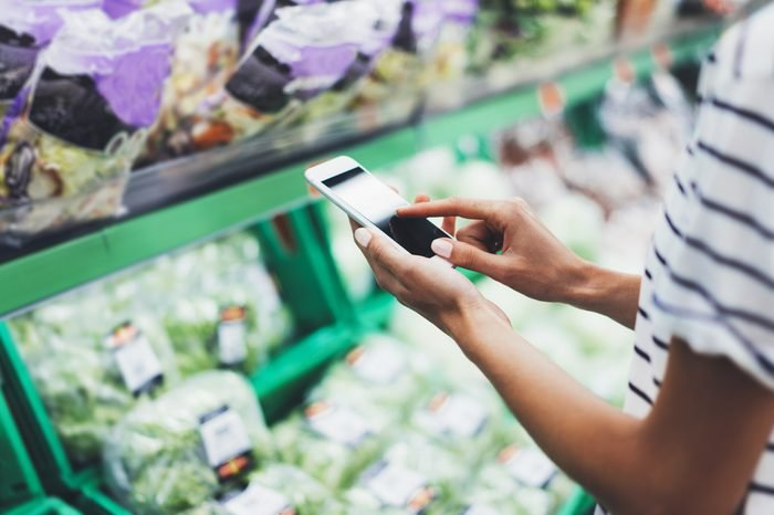 Woman shopping healthy green food in supermarket background. Close up view girl buy products using digital gadget in store. Hipster at grocery using smartphone. Person comparing the price of produce