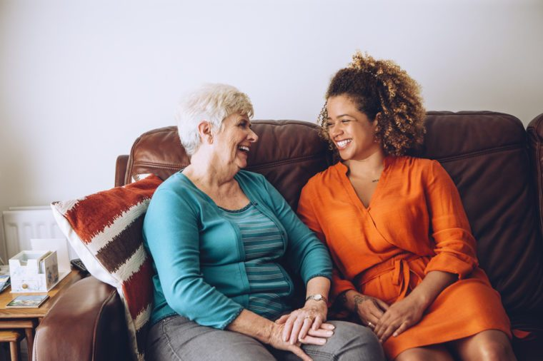 Senior woman enjoying a laugh with her granddaughter. They are sitting on the sofa together.