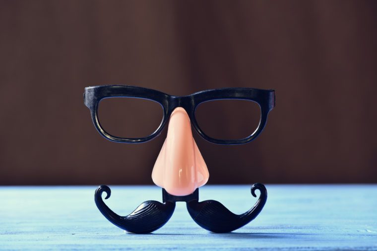 closeup of a fake mustache, nose and eyeglasses on a rustic blue wooden surface